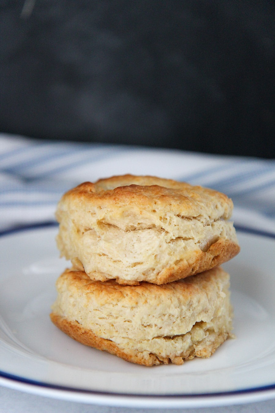 two buttermilk biscuits stacked on top of each other on a white and blue plate.