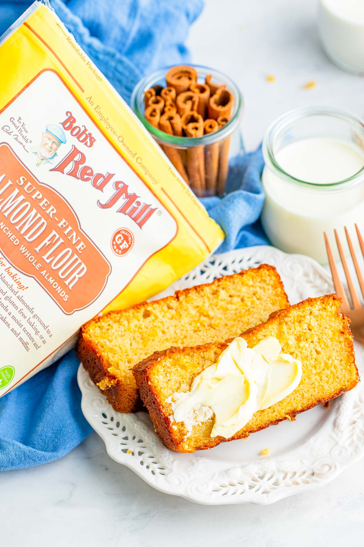 two slices of sweet potato bread with butter, a fork on the side, a glass of milk, and a package of bobs red mill almond flour.
