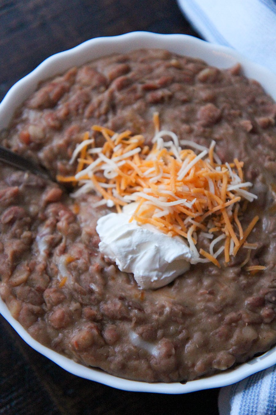 beans in a white bowl with sour cream and cheese on top.