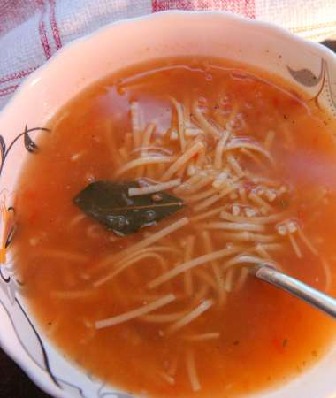 a bowl of sopa de fideo with a spoon and a red and white towel on the side.