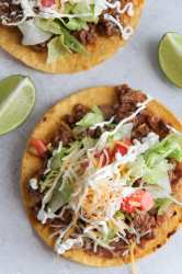 beef tostadas up close with two lime wedges.