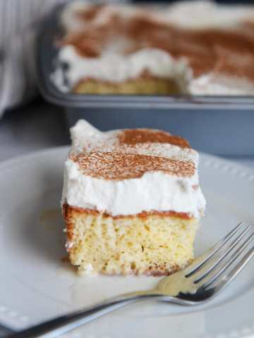 a slice of coquito cake up close with a fork on the side.