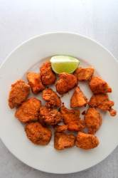chicharron de pollo aka chicken bites on a white plate with a lime wedge.