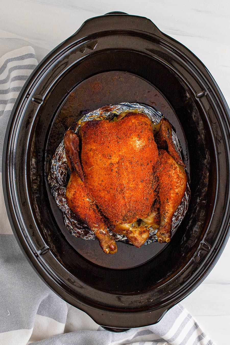 slow cooker whole chicken on top of aluminum foil.