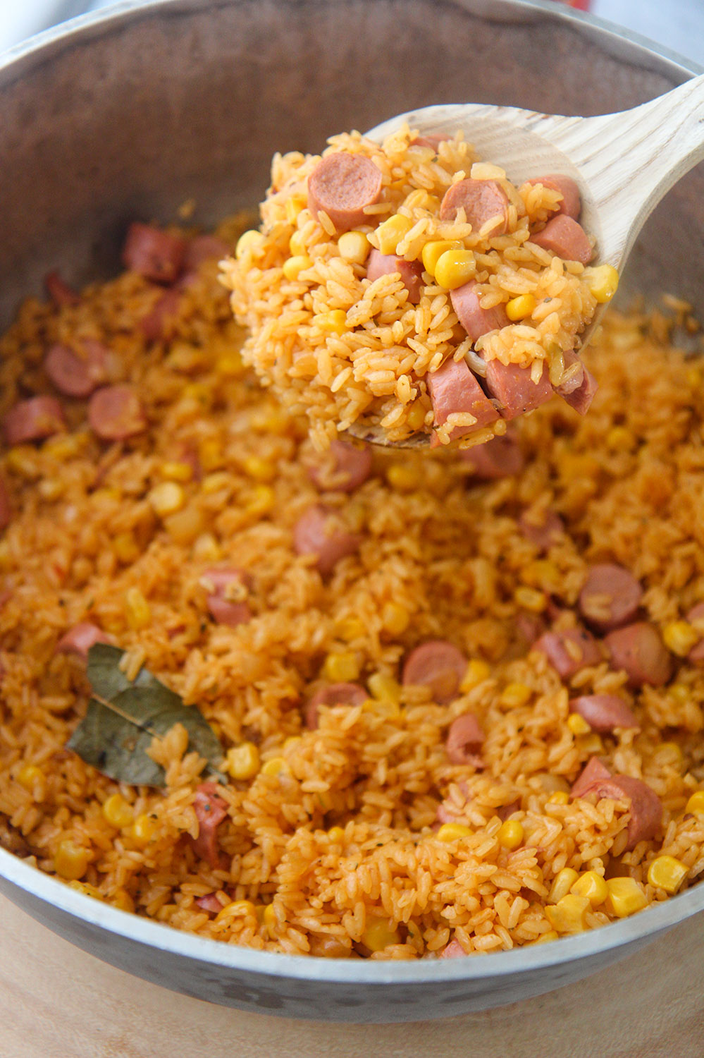a wooden spoon filled with arroz con salchichas.