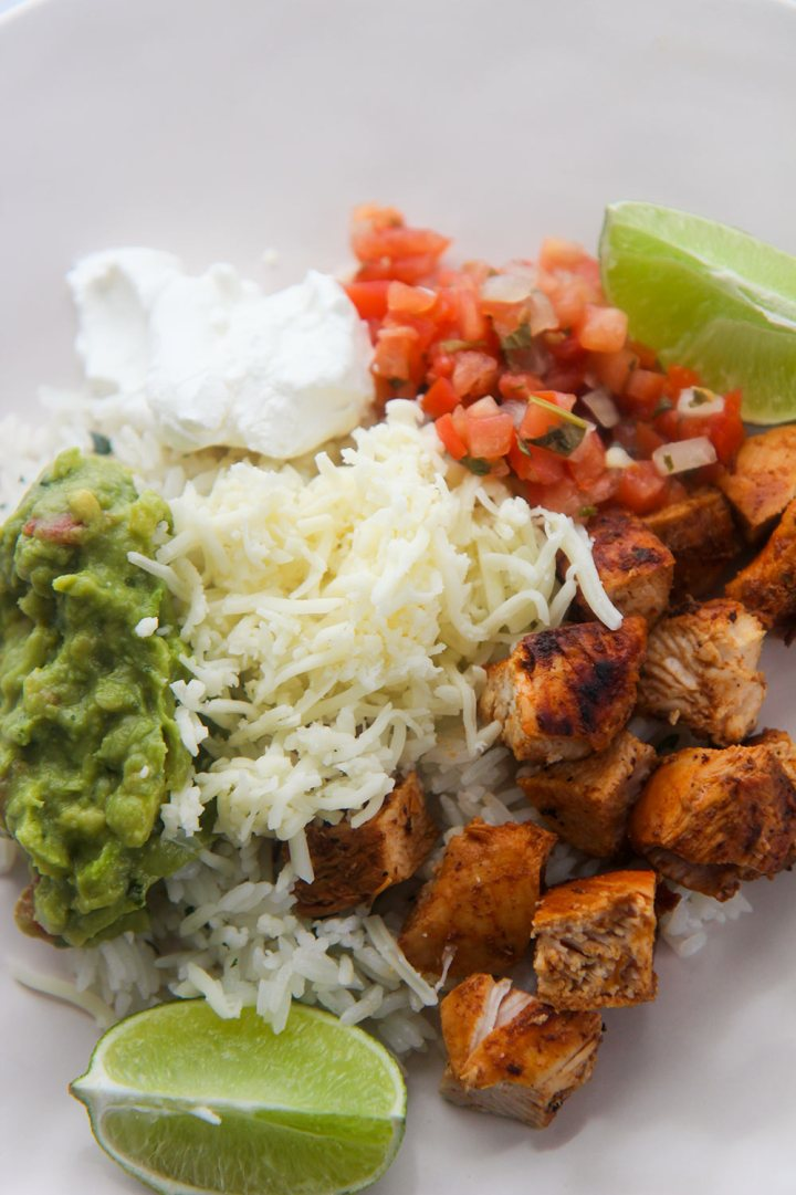 guacamole, cheese, pico de gallo, chicken, sour cream, and lime wedges on a plate.