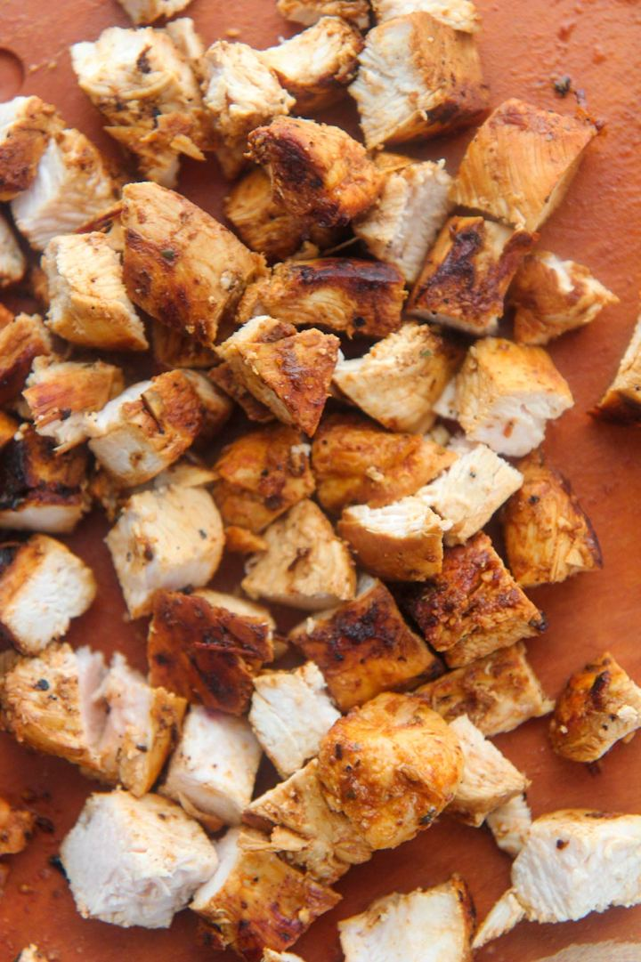 diced up chicken on a wooden board.