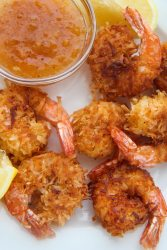 six fried coconut shrimp with orange sauce and lemon wedges on the side.