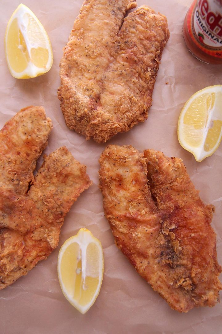 three fried tilapias on brown parchment paper.