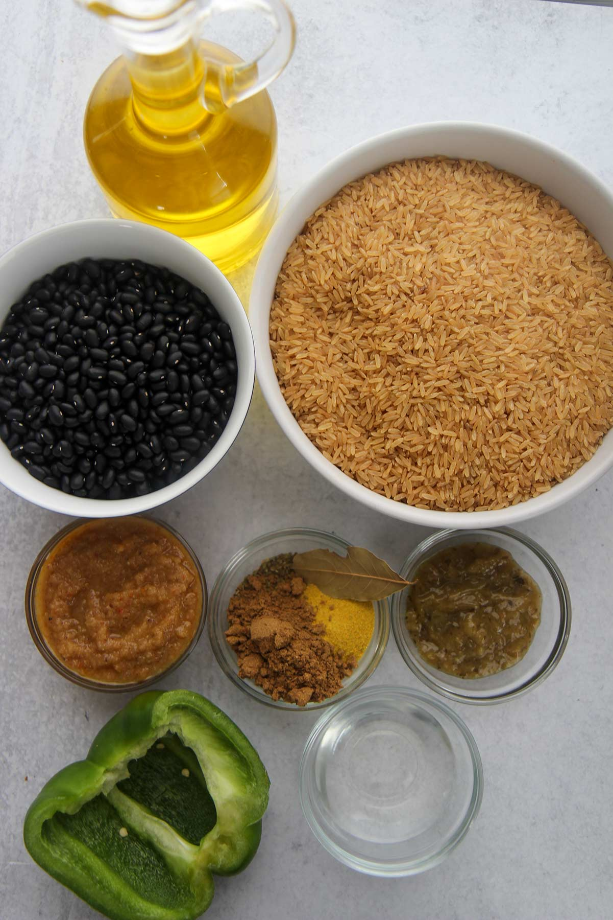 ingredients for congri, dried black beans, brown rice, small bowls with spices, vinegar, bay leaf, sofrito, and recaito. Oil and a green bell pepper.
