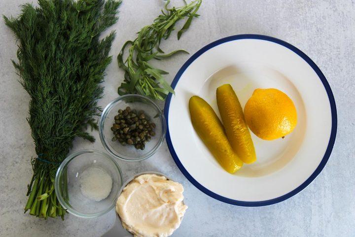 pickles, lemon, mayo, capers, sugar, tarragon, and dill. Ingredients to make tartar sauce.