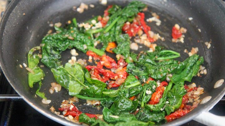 spinach, onions, garlic, and sun dried tomatoes in a skillet.