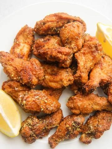 honey lemon pepper wings on a white plate with lemon wedges