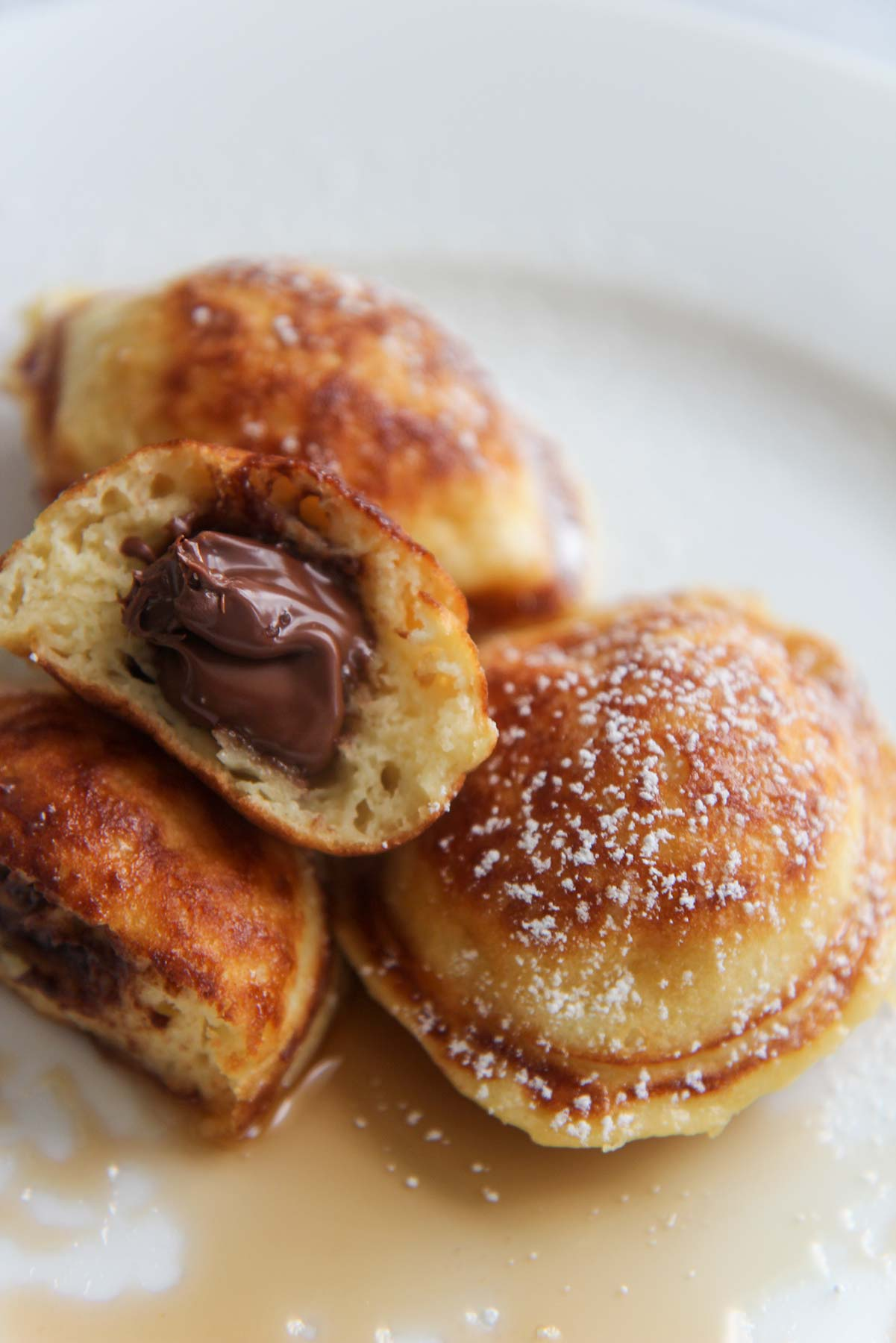 Nutella stuffed pancakes up close with powdered sugar on top.