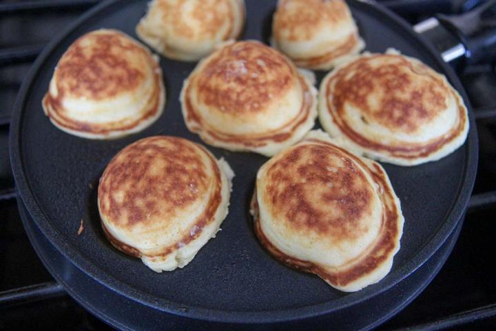 seven mini pancakes cooking in a pan.