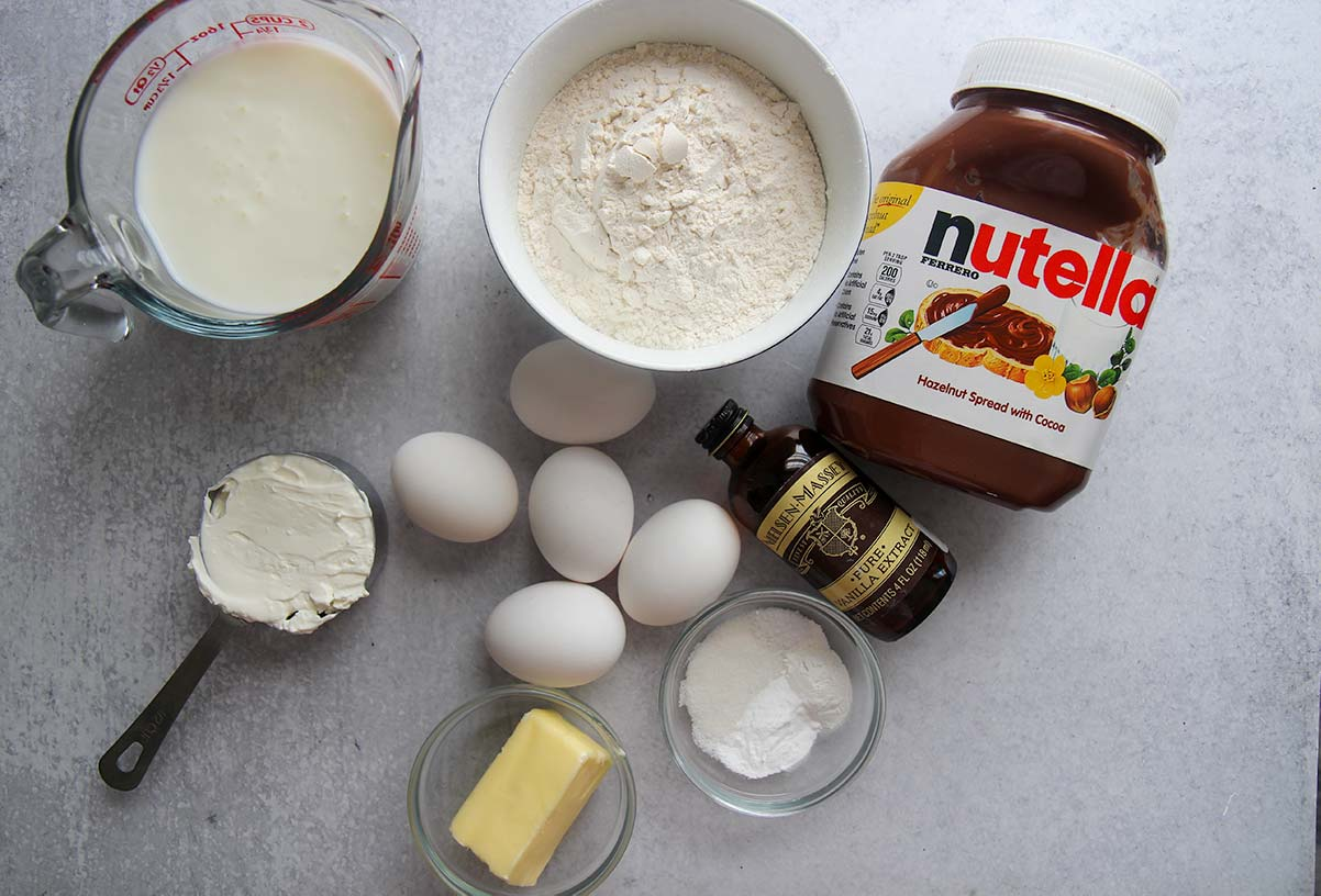 Ingredients to make Nutella stuffed Danish pancakes. Eggs, buttermilk, butter, Nutella, flour, sour cream, and vanilla extract.