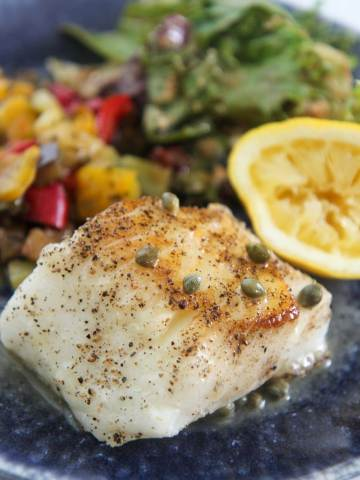Chilean sea bass with vegetables, salad, and lemon.