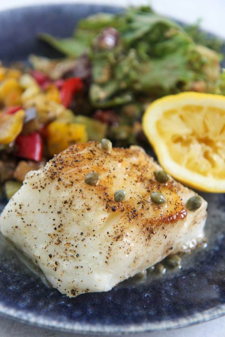 Pan-seared Chilean sea bass, salad, vegetables, and lemon on a blue plate.