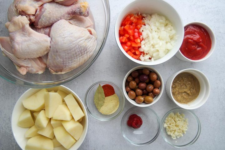 raw chicken in a glass bowl and other ingredients in small bowls.