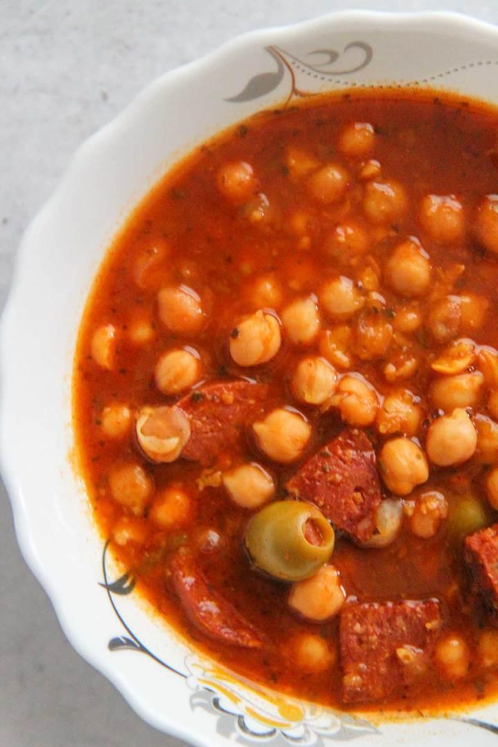 Garbanzos guisados with chorizo and olives up close.