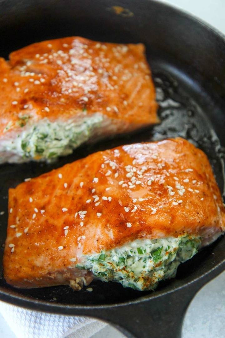 Two spinach stuffed salmon fillets in a cast-iron skillet.