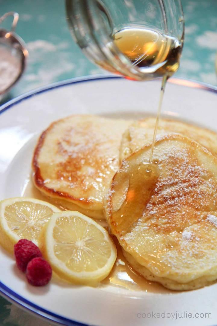 lemon ricotta pancakes with syrup, raspberries, and lemon slices.