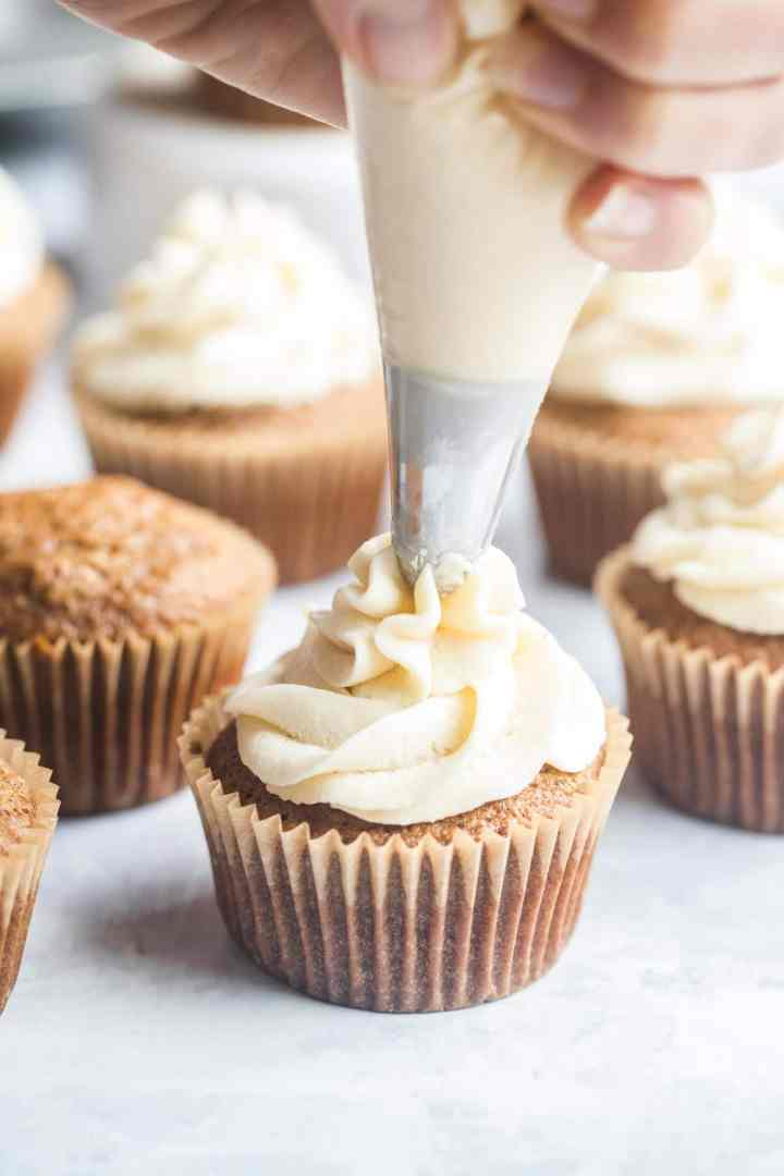 piping bag filled with cream cheese frosting, frosting a cupcake.
