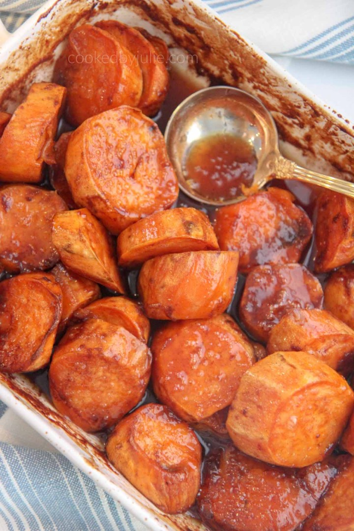 candied yams in a casserole dish with a spoon.