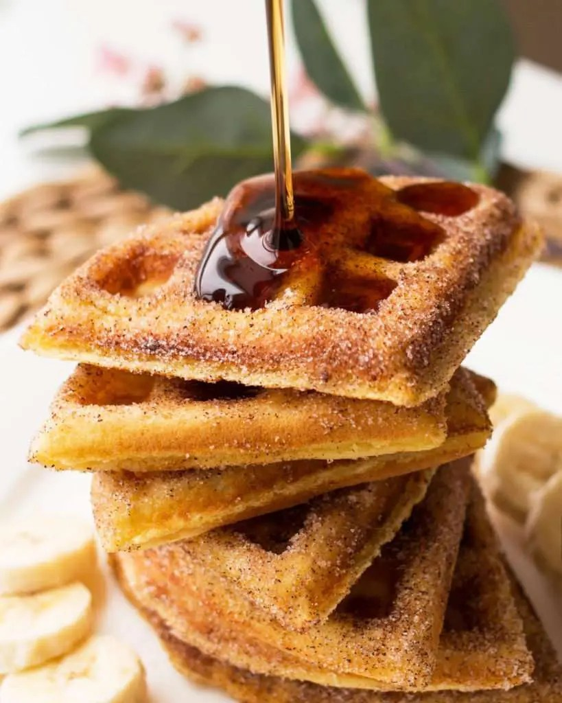 close-up photo of churro waffles with syrup pouring on top