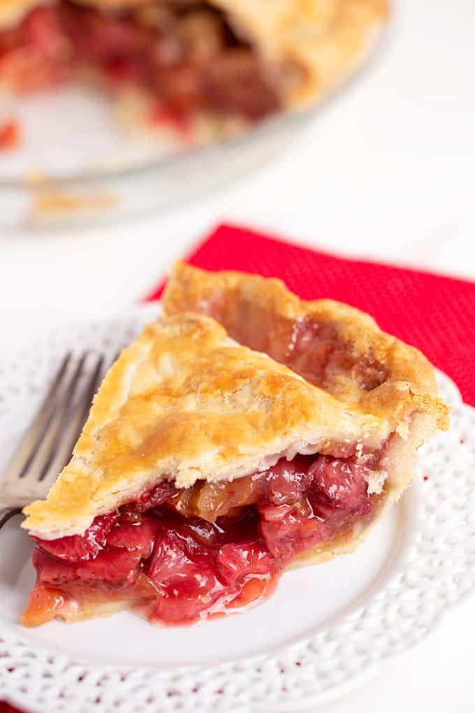 slice of pie on a white dessert plate with a red linen under the plate