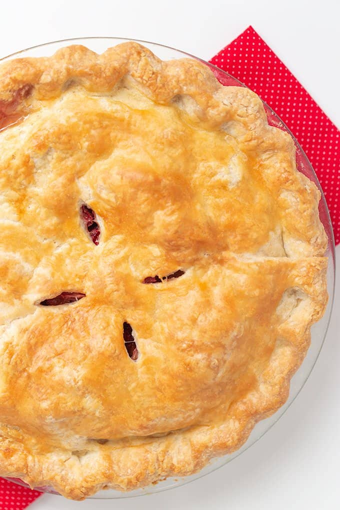 overhead photo of the whole pie on a red linen on a white surface
