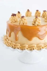 Photo of carrot cake with caramel buttercream on a white ruffled cake plate.