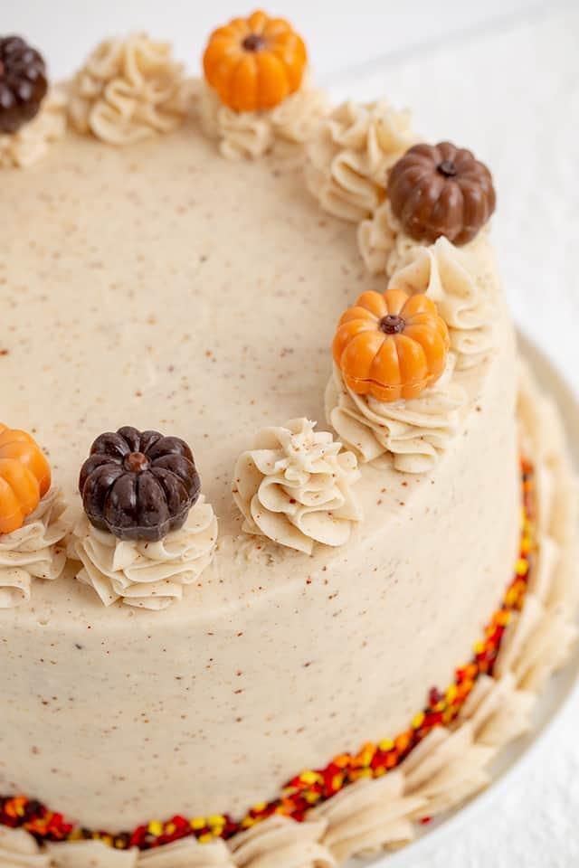 close up of pumpkin truffles on top of a pumpkin spice cake