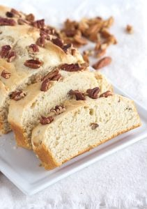 two slices of 4 ingredient ice cream bread on a white plate with pecans