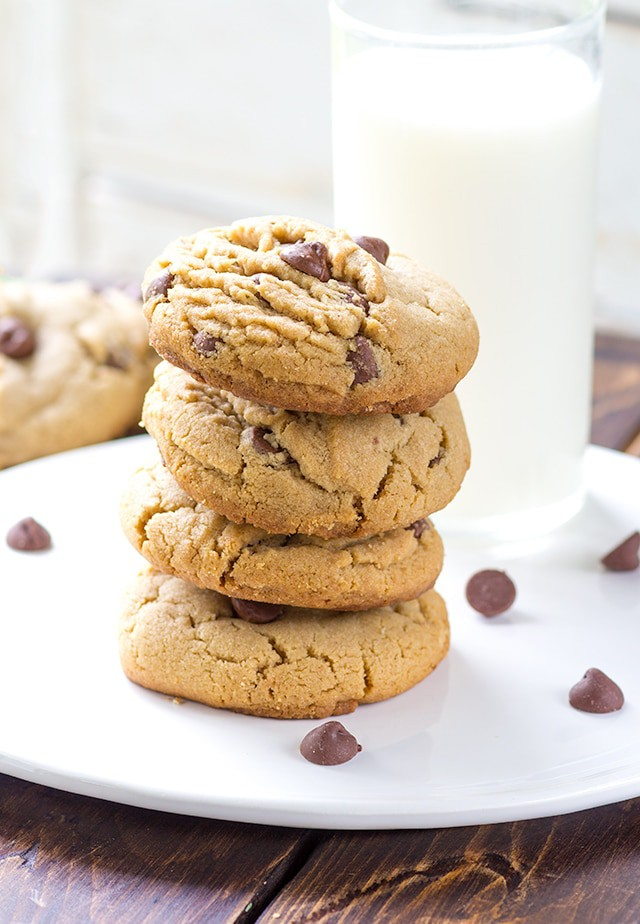 4 peanut butter chocolate chip cookies stacked onto a white plate. Chocolate chips scattered around the plate