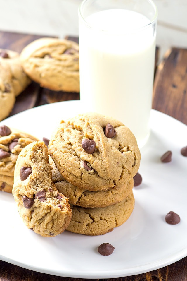 white plate with a stack of peanut butter chocolate chip cookies. One cookie has a bite taken out of it