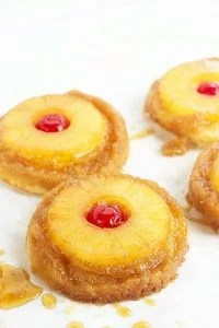 Pineapple Upside Down Sugar Cookies - Pineapple upside down cake in cookie form because everyone loves cookies! Soft sugar cookie bottoms with a ring of pineapple and cherry center all covered in a brown sugar glaze!