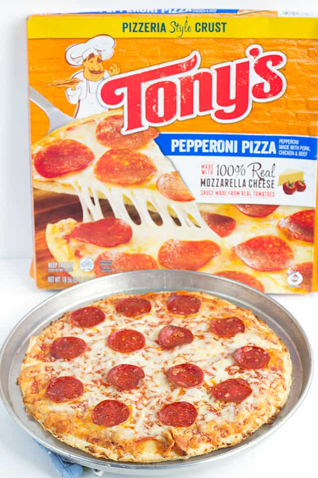 a pepperoni pizza on a sheet pan next to a Tony's pepperoni pizza box