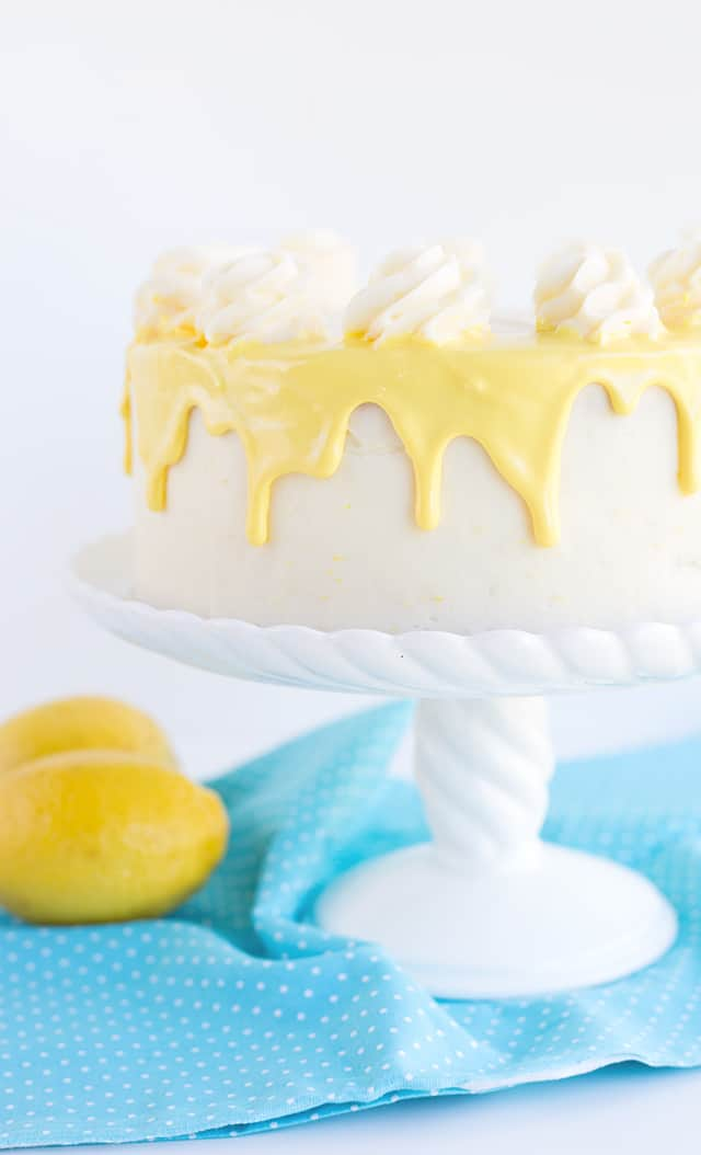 yellow colored white chocolate ganache dripping down the sides of a 2-layer olive oil cake