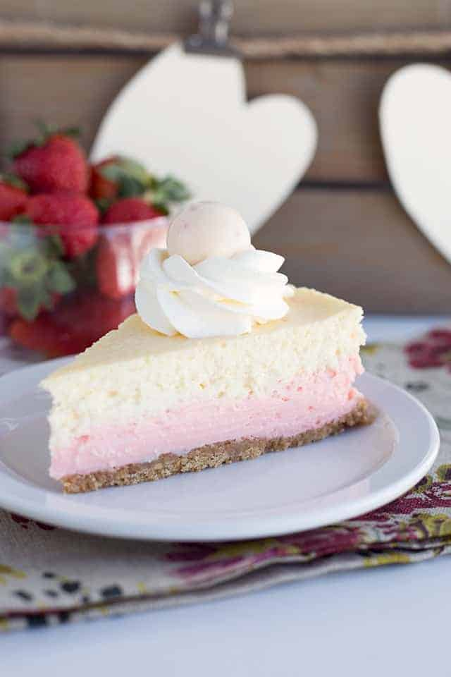 a slice of strawberries and cream cheesecake sitting on a plate with a floral napkin underneath and strawberries in a glass bowl behind it