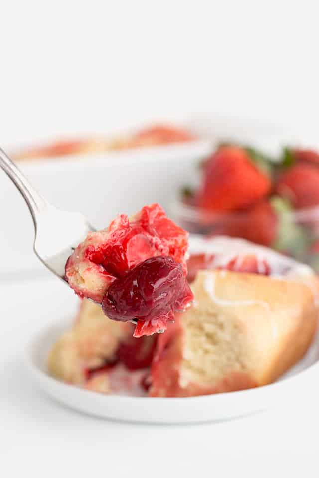 A fork full of the strawberry sweet rolls with a strawberry is in focus. In the background is a sweet roll on a white plate, strawberries in a bowl, and the white pan.
