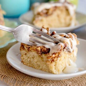 fork full of apple fritter cake on white plate