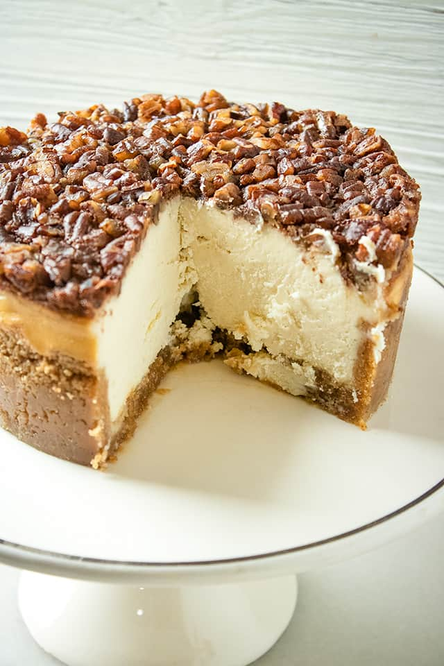 instant pot pecan pie cheesecake on a white cake plate with a slice missing