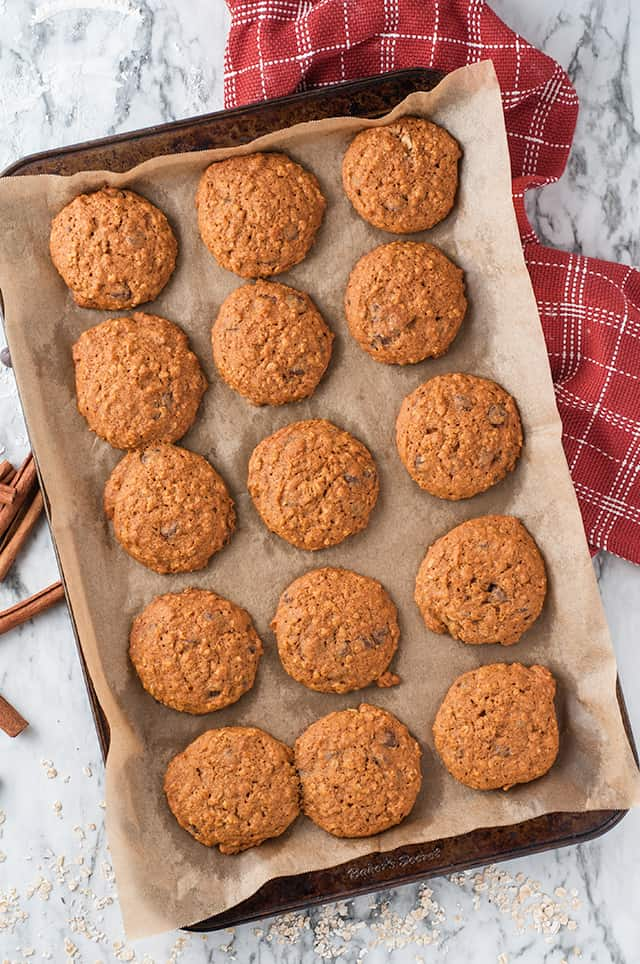 pumpkin oatmeal chocolate chip cookies on baking sheet with parchment paper