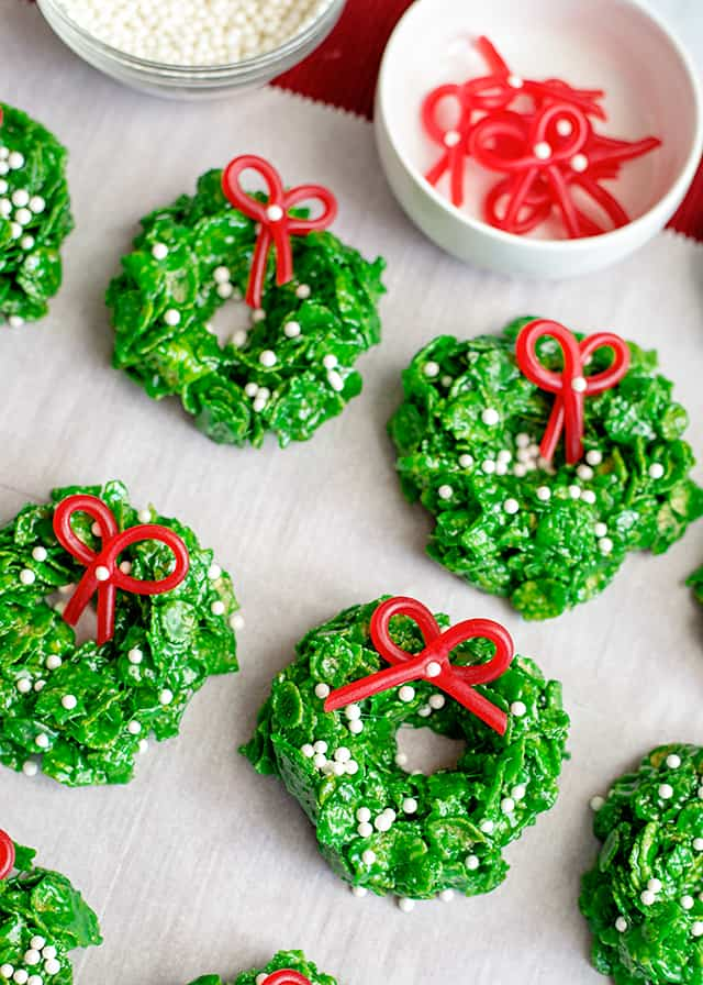 Christmas Wreath Cookies on parchment paper with candy bows in white dish