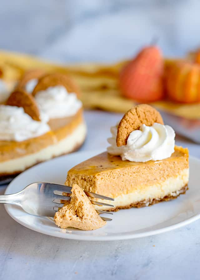 fork full of double layer pumpkin cheesecake on white plate