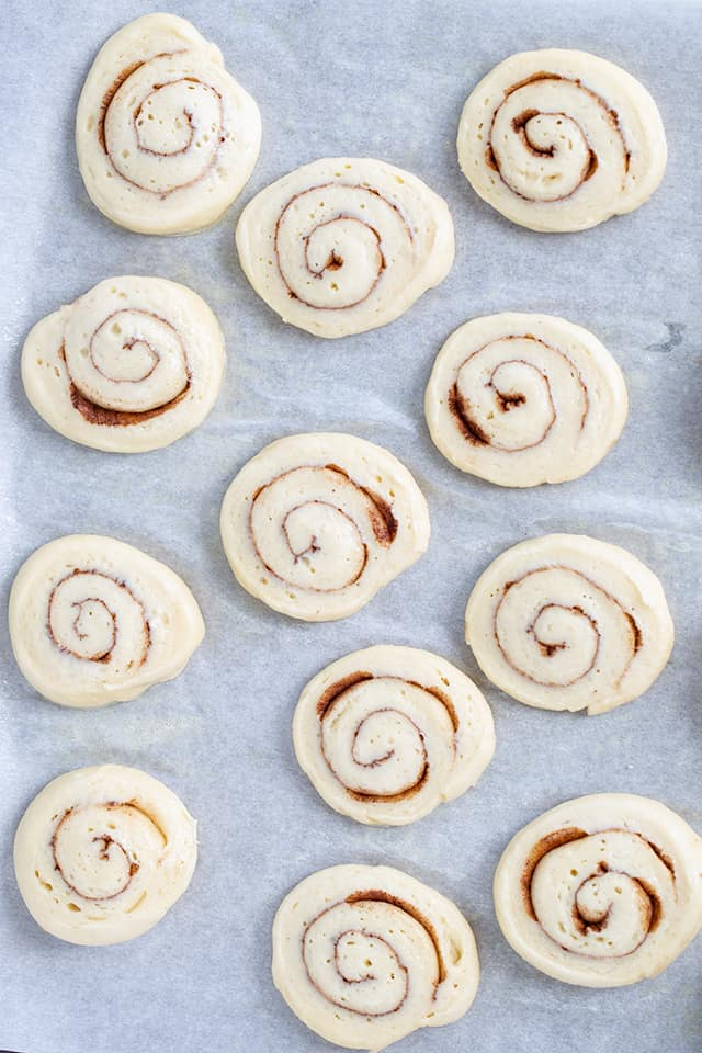 raw honey buns on a parchment lined baking sheet