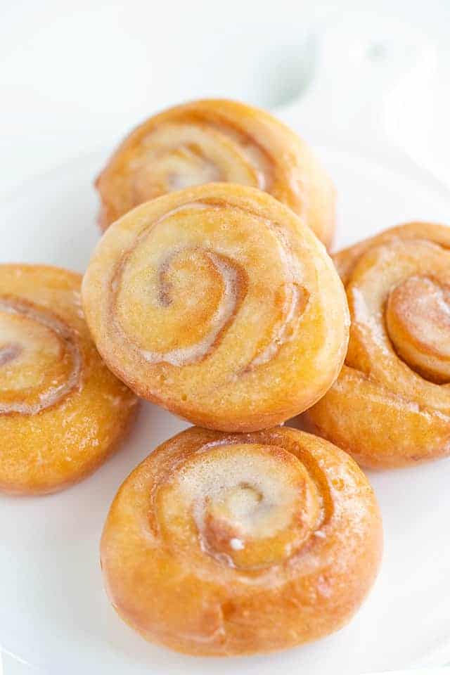 honey buns stacked on a white platter