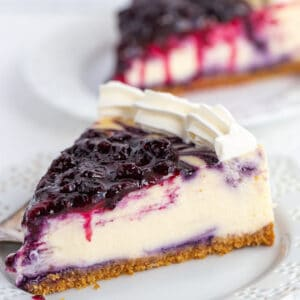 slice of blueberry cheesecake on a white lace plate with a drizzle of blueberry sauce dripping down the cheesecake