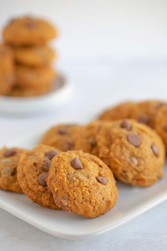 plate of pumpkin cookies with a stack of cookies on a white plate in the background